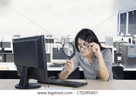 Young businesswoman looking at a computer with a magnifying glass in the office