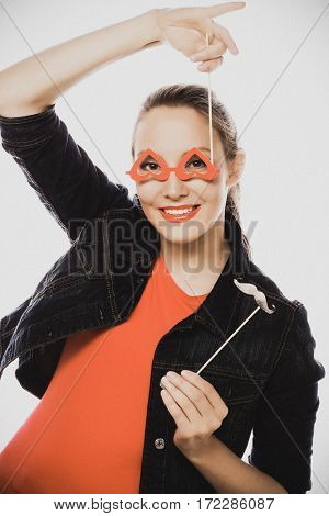 Attractive playful young woman holding mustache and glasses on a stick. Ready for party.Special fashion color processing.