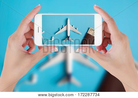 Woman hand using smart phone taking photo for preparation traveling with airplane money passport earphone and book. Travel concepts Ambient blurry background.