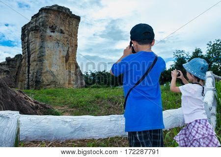 Back View Of Asian Children Taking Photos By Camera.