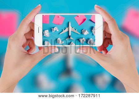 Woman hand using smart phone taking photo for preparation Traveling with airplane model flying among paper clouds and pink paper noted. Travel concepts Ambient blurry background.