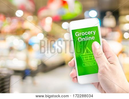 Hand Holding Mobile With Grocery Online On Screen With Blur Supermarket Background, Online Delivery