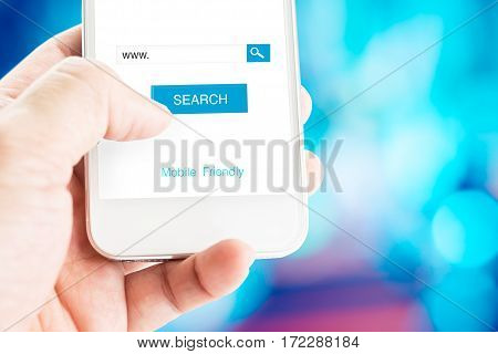 Hand Holding Mobile Phone With Search Page On Screen With Mobile Friendly Feature At Blurred Blue Ba