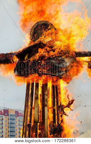 Burning scarecrow of Shrovetide in bright flame on background of city building and sky