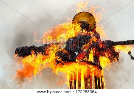 Burning down scarecrow of Shrovetide in bright flame