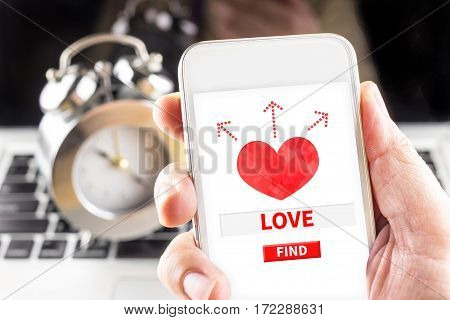 Hand Holding Mobile With Red Heart And Find Love Word On Screen With Clock And Laptop At Background,