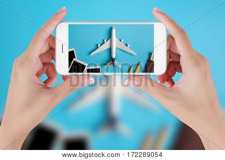 Woman hand using smart phone taking photo for preparation traveling with Blank photograph airplane money passport pencils and book. Travel concepts Ambient blurry background.