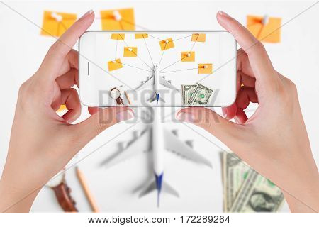 Woman hand using smart phone taking photo for preparation traveling network with push pin pencil watch money dollar string paper noted. Travel concepts Ambient blurry background.