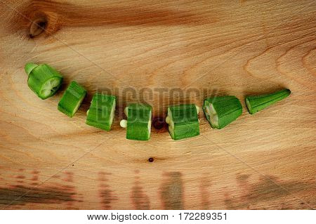 Close-up image of okra cut into pieces placed on wood