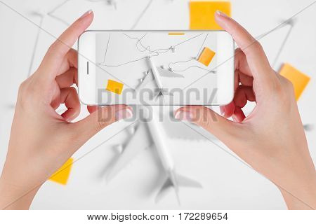 Woman hand using smart phone taking photo for preparation traveling network with push pin string and paper noted . Travel concepts Ambient blurry background.