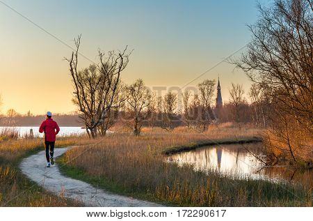 Jogger running on lakeside footpath for outdoor exercise in nature park. Meadows trees and church in background are lit by early morning sun at sunrise.