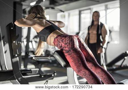 Sportive girl with long hair does lifting on the trainer in the gym on the blurry background of the windows and other visitor. She wears a black top and coral pants with patterns. Horizontal.