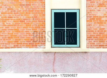 Blue window at orange brick wall of house.