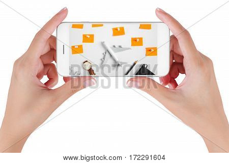 Woman hand using smart phone searching Preparation traveling and to do list the paper noted airplane pencil book earphone and push pin. Travel concepts Isolated on white background.