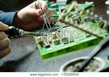Male hands close up soldering a microchip. soldering iron