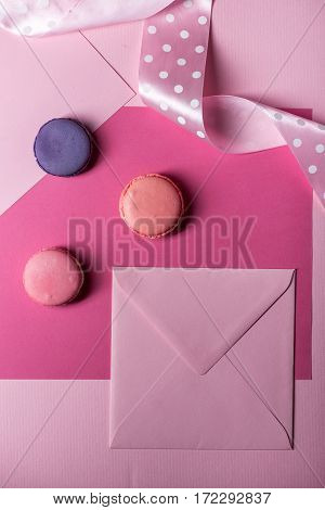 Pink envelope and macoron cookies on pink background