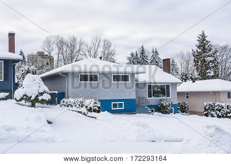 Family residential house with front yard in snow. North American house on winter cloudy day