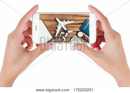Woman hand using smart phone searching Preparation traveling with pencil watch money passport airplane noted book and earphone on vintage wooden background. Travel concepts.