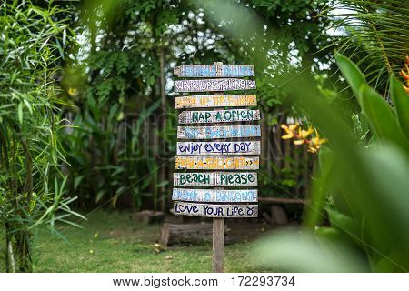 Wooden signboard with multi-colored inscriptions on the green nature background. Inscriptions are cyan, orange, green, violet. Outdoors. Horizontal.