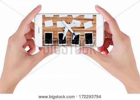 Woman hand using smart phone searching Preparation traveling and to do list with paper noted airplane and photo frame on vintage wooden background. Travel concepts Isolated on white background.