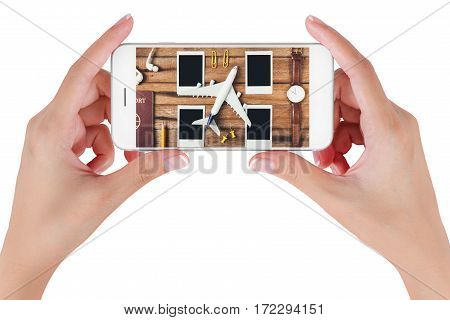 Woman hand using smart phone searching preparation traveling with pencil passport airplane watch blank photographs and earphone on vintage wooden background. Travel concepts.