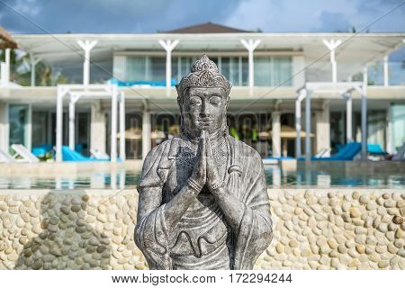 Stone buddha statue on the blurry background of the hotel and the pool. Sun shines on the statue and it casts shadow on the pool's part. Horizontal.