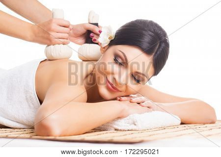 Beautiful, young and healthy woman on bamboo mat in spa salon is having massage. Isolated on white. Spa, health and healing concept.