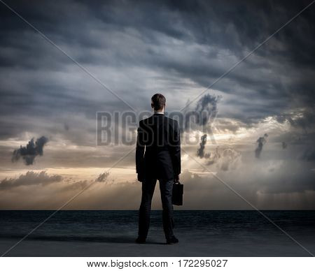 Businessman with briefcase standing over dark, dramatic ocean background. Business concept.
