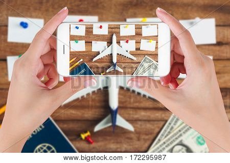 Woman hand using smart phone taking photo for preparation traveling and to do list with paper noted pencil money passport airplane colorful push pin on vintage wooden background. Travel concepts.