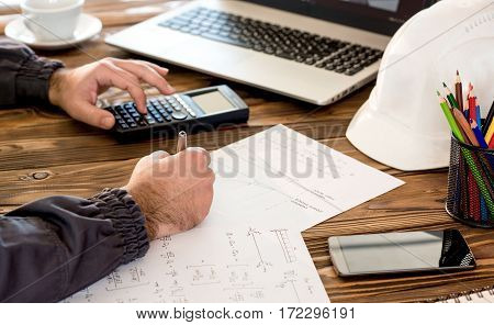 Civil Design Engineer is making structural analysis calculations using a scientific calculator.