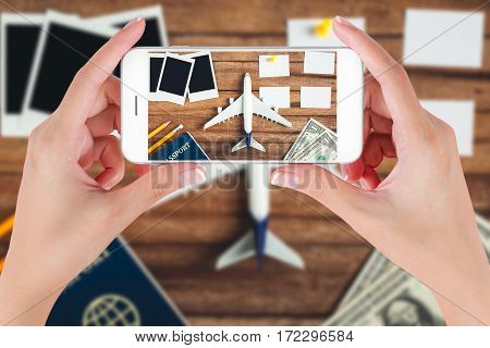 Woman hand using smart phone taking photo for preparation traveling and to do list with paper noted pencil money passport airplane push pin and blank photographs on vintage wooden background.
