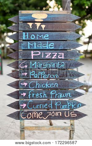 Dark wooden signboard with multi-colored inscriptions of the pizza menu. Inscriptions are cyan, pink and orange. Closeup. Vertical.