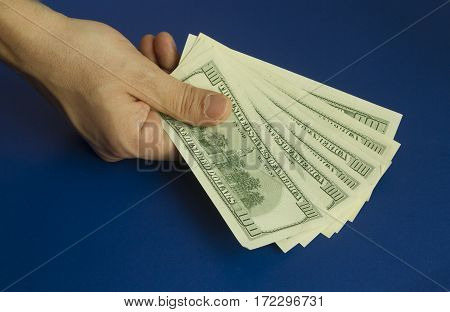 Man's hands holding dollars on dark blue background