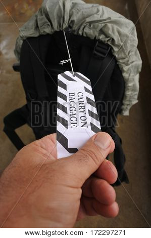 Man hand holds a Carry-on baggage baggage tag in Airport before flight. Travel concept.