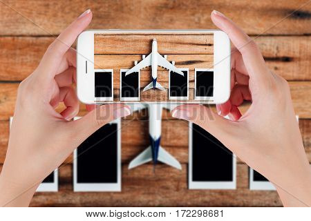 Woman hand using smart phone taking photo for preparation traveling with airplane and photo frame on vintage wooden background. Travel concepts blurry background.