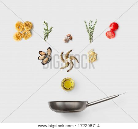 Cooking italian food, seafood pasta, isolated on white. Frutti di mare with fettuccine spaghetti. Mussels, prawn, shrimp, calamari rings and other ingredients over frying pan