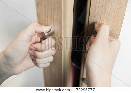 Closeup Hands of woman is holding on door handles of cabinet Door handles of closet or wardrobe