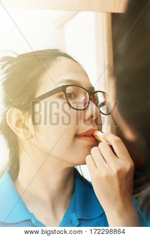 Portrait of asian girl applying makeup. Beautiful asian girl looking in the mirror and applying red lipstick. Eyeglasses girl applying lipstick.