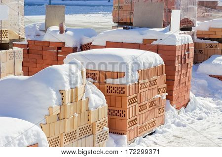 Several pallets of the red perforated bricks with round and rectangular holes covered snow on an outdoor warehouse in winter sunny day
