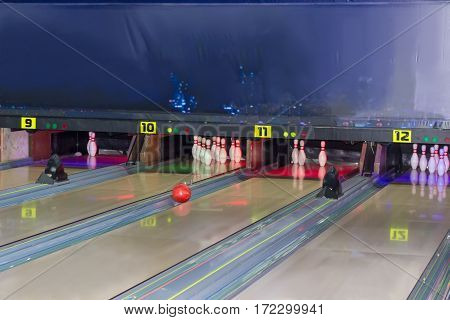 Fragment of several lanes rolling along the gutter bowling ball and bowling pins in a modern pin bowling alley