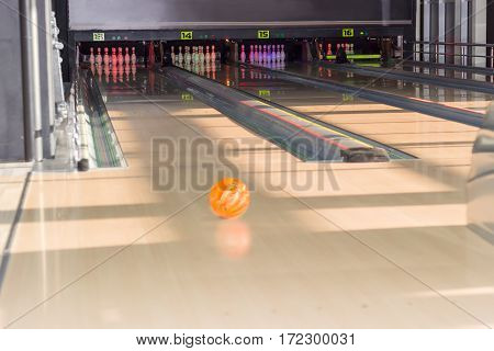 Several lanes with bowling pins and bowling ball on the foreground in a modern pin bowling alley