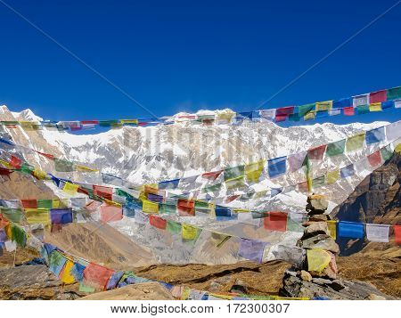 View of the south face of Annapurna I Main Mountain across the colorful prayer flags on the background of sky in morning in the Himalayas