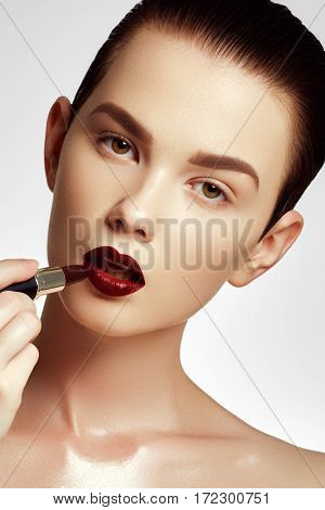 Cosmetics And Makeup. Fashion Model Applying Makeup. Beautiful Young Woman With Wine Lipstick. Model