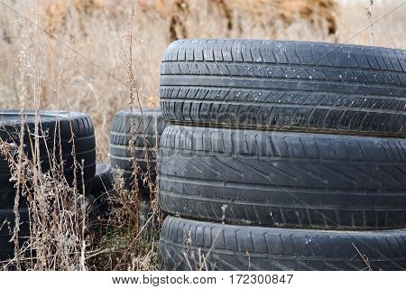 Closeup of several worn tires placed in the grass