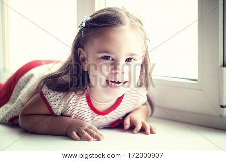 Little smiling child girl watching out the window. Portrait of cheerful kid lying on windowsill