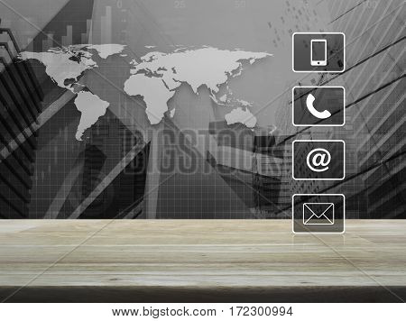 Telephone mobile phone at and email buttons on wooden table over world map with financial graph and city tower Customer support concept Elements of this image furnished by NASA