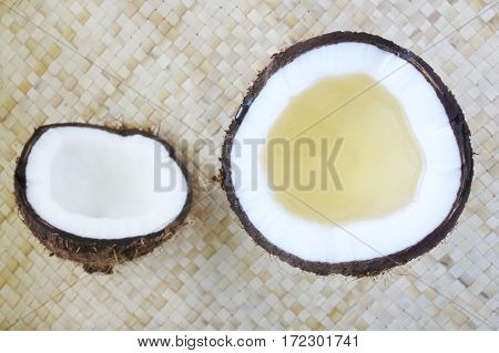 Flat Lay Of Open Coconut Palm Fruit With Coconut Oil In It