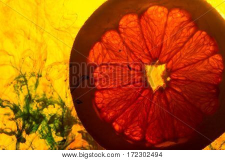 close up of a grapefruit slice in water