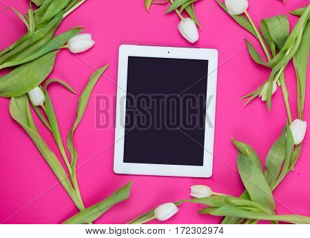 beautiful tablet and tender white tulips lying on the wonderful pink background