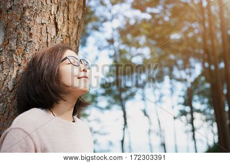 Happiness concept. Woman smiling and breathing fresh air with natural tree background.